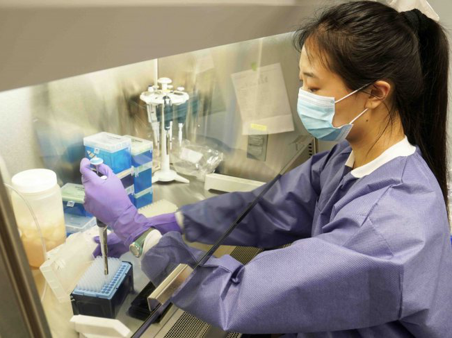 angela yang with pipette at a lab work station