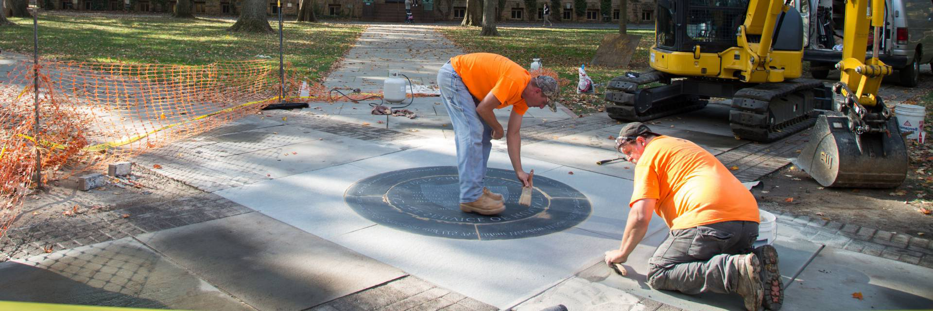 Workers installing University motto medallion outside Nassau Hall